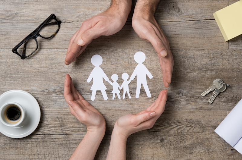 Two pairs of hands encircling a paper cut-out of a family.