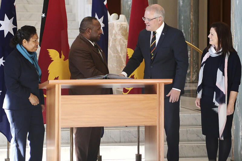 Papua New Guinea's Prime Minister James Marape, second from left, shakes hands with Australian Prime Minister Scott Morrison, watched by their respective wives Rachael Marape, left, and Jenny Morrison after signing the visitors' book at Australia's Parliament House in Canberra Monday, July 22, 2019. Marape says his country's relationship with China in not open to discussion during his current visit to Australia. (AP Photograph/Rod McGuirk)