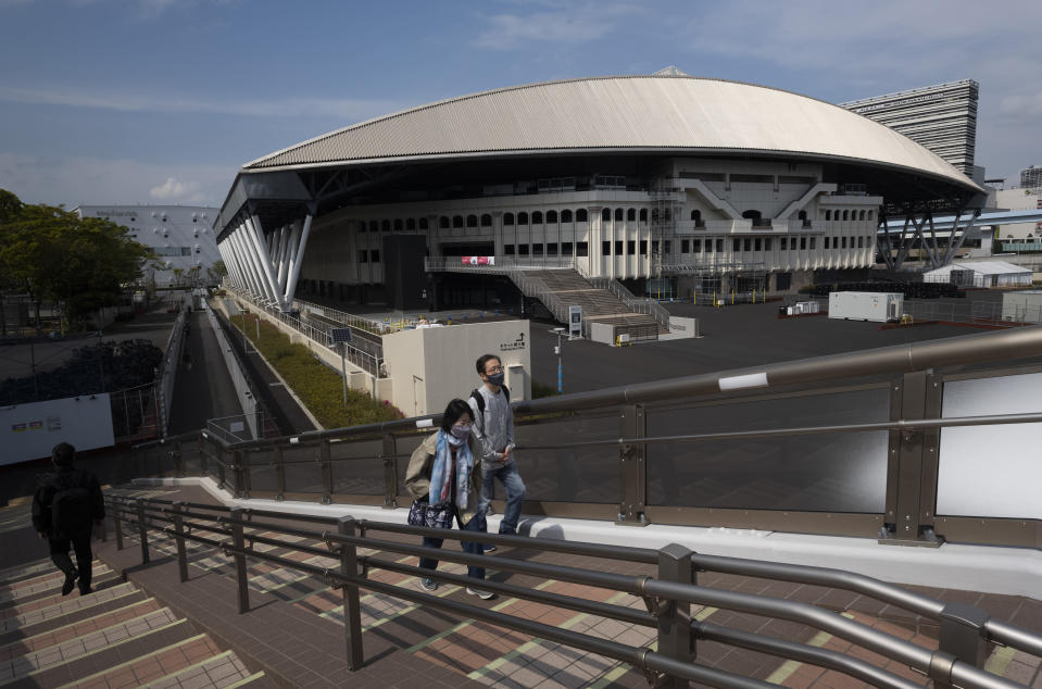 People walk past Ariake Colosseum, a venue planned to be used for the postponed Tokyo 2020 Olympic and Paralympic Games, in Tokyo Thursday, April 8, 2021. Many preparations are still up in the air as organizers try to figure out how to hold the postponed games in the middle of a pandemic. (AP Photo/Hiro Komae)