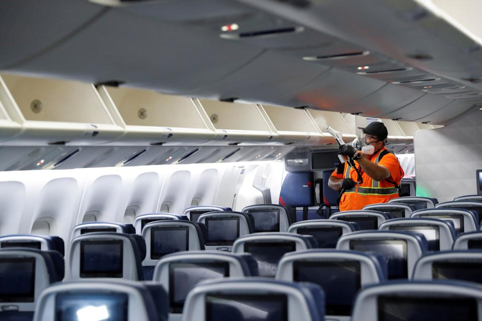 A Delta Air Lines pre-flight cleaning crew member uses an electrostatic disinfection device to clean an aircraft at JFK International Airport in New York, U.S., August 6, 2020. Picture taken August 6, 2020. REUTERS/Shannon Stapleton
