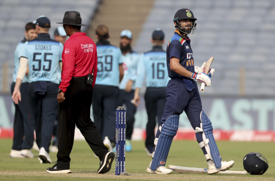 India's captain Virat Kohli, right, walks off the field after being dismissed by England's Mark Wood during the first One Day International cricket match between India and England at Maharashtra Cricket Association Stadium in Pune, India, Tuesday, March 23, 2021. (AP Photo/Rafiq Maqbool)