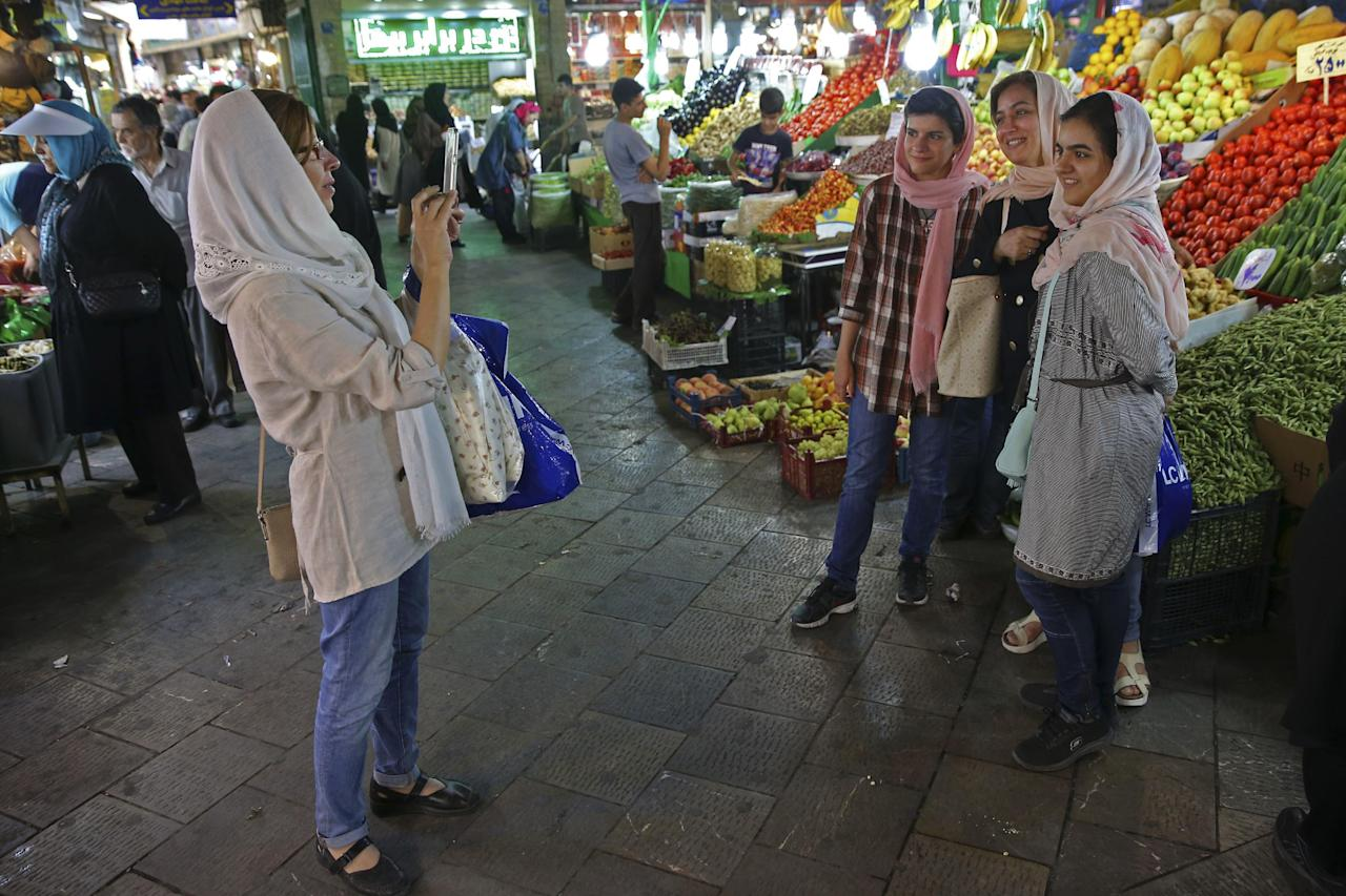 """FILE - In this Tuesday, July 19, 2016 file photo, Iranian women take a picture in Tajrish bazaar in northern Tehran, Iran. Iran's foreign minister on Tuesday extolled the country's ability to bring its nuclear program back on track as limits on the landmark 15-year accord between Tehran and world powers ease in the coming years. Mohammad Javad Zarif said a document, submitted by Iran to the International Atomic Energy Agency and outlining plans to expand Iran's uranium enrichment program, is a """"matter of pride."""" The document, obtained by The Associated Press in Vienna, outlines Tehran's plans to expand its uranium enrichment program after the first 10 years of the nuclear deal. (AP Photo/Vahid Salemi, File)"""