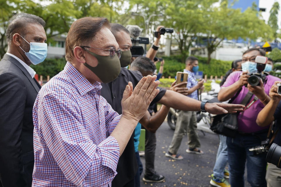 Malaysian opposition leader Anwar Ibrahim gestures after speaking to media outside police headquarters in Kuala Lumpur, Malaysia, Friday, Oct. 16, 2020. Anwar was questioned by police over the dissemination of a purported list of lawmakers supporting his bid to oust the government. (AP Photo/Vincent Thian)