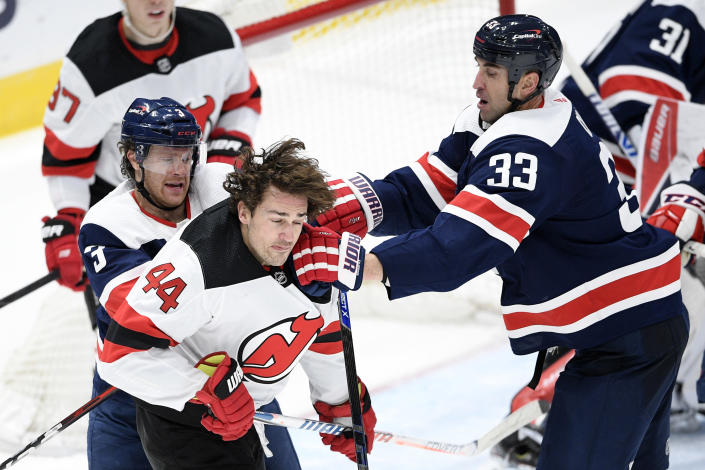 Washington Capitals defenseman Zdeno Chara (33) and defenseman Nick Jensen (3) scuffle with New Jersey Devils left wing Miles Wood (44) during the second period of an NHL hockey game, Sunday, Feb. 21, 2021, in Washington. (AP Photo/Nick Wass)