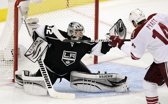 Los Angeles Kings goalie Jonathan Quick, left, stops a shot as Phoenix Coyotes left wing Taylor Pyatt watches during the second period of Game 4 of the NHL hockey Stanley Cup Western Conference finals in Los Angeles, Sunday, May 20, 2012. (AP Photo/Jae C. Hong)
