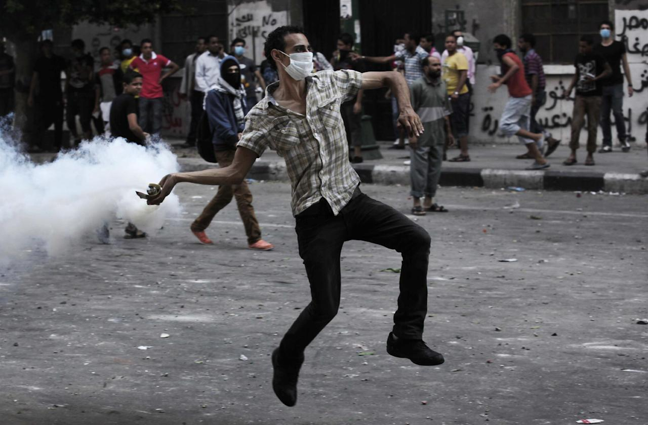 An Egyptian protester throws back a tear gas canister toward riot police, unseen, outside the U.S. embassy in Cairo, Egypt, Thursday, Sept. 13, 2012. Tens were injured in clashes in front of the U.S. embassy in Cairo, the state TV reported on Thursday, quoting Egypt's Health Ministry. (AP Photo/Nasser Nasser)