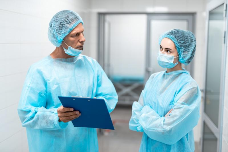 Two professional doctors in blue medical uniform standing in front of each other in hospital corridor and looking thoughtful