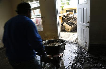 A man carries mud out of a home damaged by a flood using a wheelbarrow in Evans, Colorado September 23, 2013. REUTERS/Rick Wilking