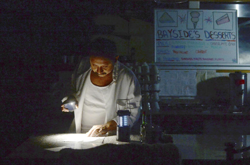 """FILE - In this Wednesday, Oct. 9, 2019, file photo, Carlos Lama of Bayside Cafe, which was among businesses to lose power due to Pacific Gas & Electric Corp's public safety power shutoff, uses an LED lamp and light from his phone at the counter of the restaurant in Sausalito, Calif. California's largest utility pledged to improve communications but reminded state regulators that its """"difficult decision"""" to pre-emptively shut off power to more than 2 million people last week may have prevented deadly wildfires. (Alan Dep/Marin Independent Journal via AP, File)"""