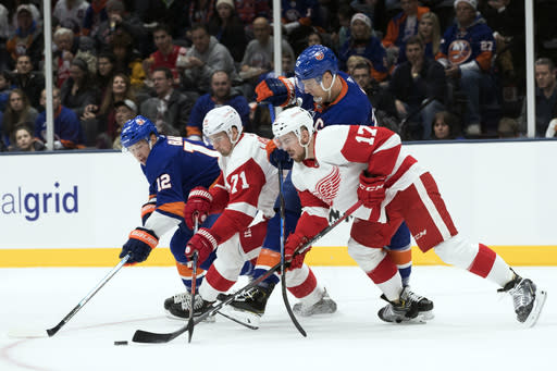 New York Islanders right wing Josh Bailey (12) and left wing Anders Lee (27) fights for the puck against Detroit Red Wings center Dylan Larkin (71) and defenseman Filip Hronek (17) during the second period of an NHL hockey game, Saturday, Dec. 15, 2018, in Uniondale, N.Y. (AP Photo/Mary Altaffer)