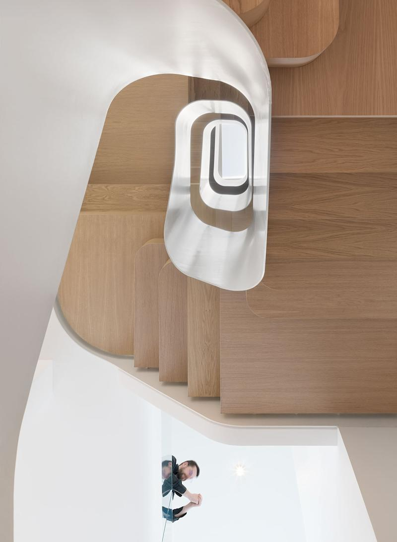 A spiraling timber staircase sits at the heart of the renovated Light Falls home