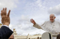 Pope Francis, right, waves as he leaves at the end of his weekly general audience, in St. Peter's Square at the Vatican, Wednesday, Nov. 27, 2019. (AP Photo/Andrew Medichini)