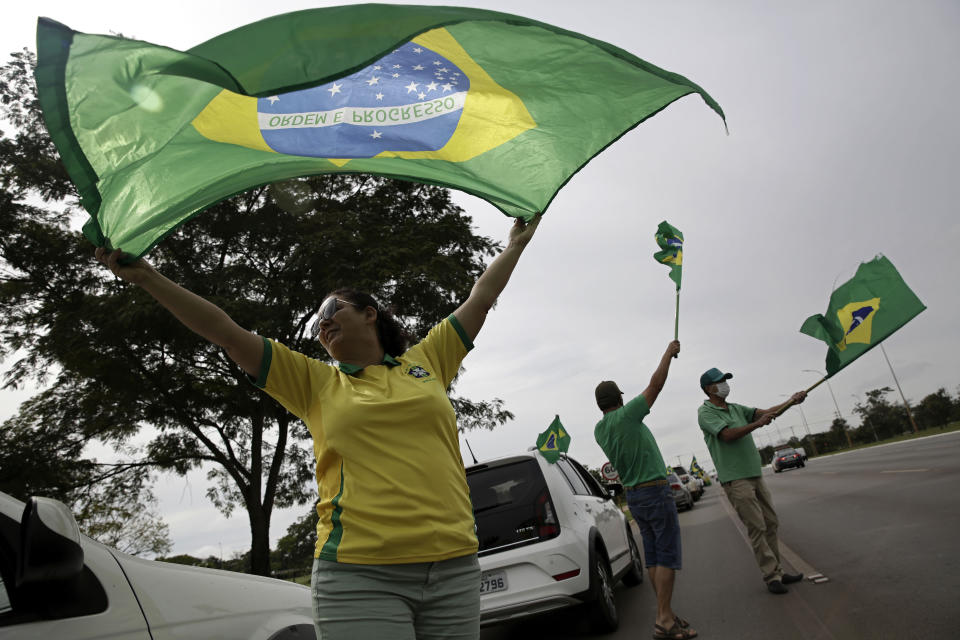People wave national flags during a demonstration backing President Jair Bolsonaro's anti-coronavirus-lockdown stance, marking May Day, or International Workers' Day, in Brasilia, Brazil, Saturday, May 1, 2021. (AP Photo/Eraldo Peres)