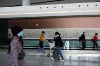 Passengers wearing face masks following the coronavirus disease (COVID-19) outbreak walk at the Beijing Daxing International Airport ahead of Chinese National Day holiday, in Beijing