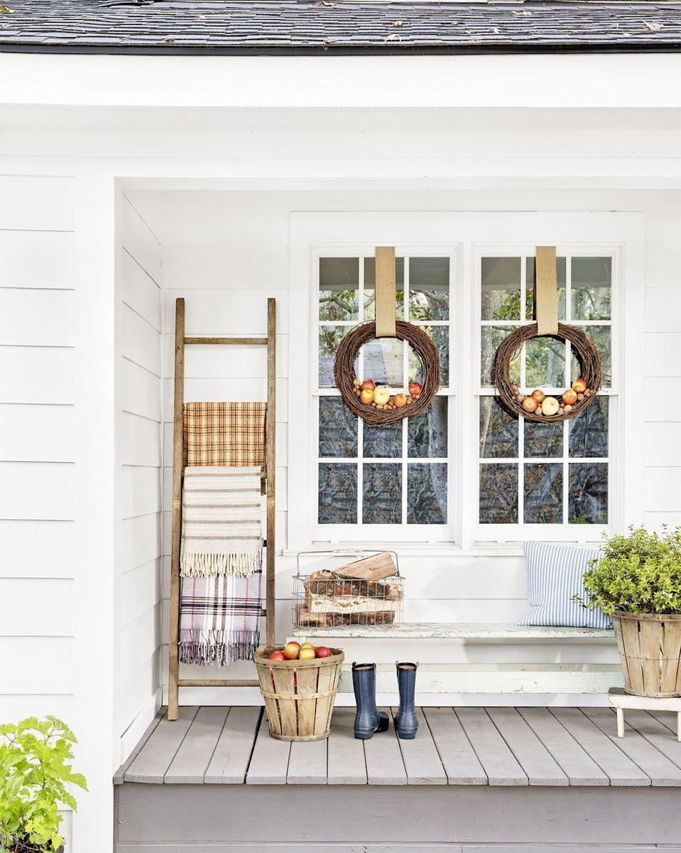 <p>This festive decoration couldn't be simpler. Just add faux apples to the bottom of a grapevine wreath (or two!), then hang and admire. Bonus: Adorn the porch with cozy blankets so you can sit outside an admire the stars on crisp fall nights. </p>