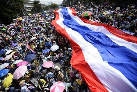 Anti-government protesters unveil a large Thai flag as they descend on Government House in Bangkok