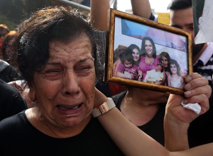 The mother of Roula Yacoub, whom her family said was killed by the daughter's husband last year, carries a picture of her daughter and grandchildren while taking part in a rally making International Woman's Day demanding that parliament approves a law that protects women from domestic violence in Beirut, Lebanon, Saturday, March 8, 2014. Although Lebanon appears very progressive on women rights compared to other countries in the Middle East, domestic violence remains an unspoken problem and the nation's parliament has yet to vote on a bill protecting women's rights nearly three years after it was approved by the Cabinet. (AP Photo/Bilal Hussein)