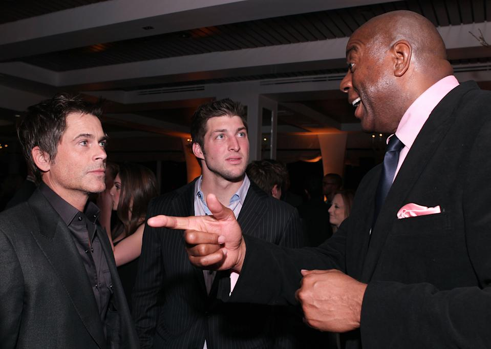 """Actor Rob Lowe, from left, NFL football player Tim Tebow and former NBA basketball player Earvin """"Magic"""" Johnson attend LL Cool J's pre-Grammy party hosted by Hennessy, on Saturday, February 11, 2012 in Los Angeles. (Chris Weeks /AP Images for Hennessy)"""