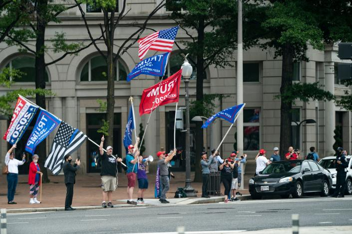 Supports of US President Donald Trump wave flags as the Presidential motorcade carrying US President Donald Trump arrives at the Trump International Hotel on September 12, 2020 in Washington, DC. - Trump will attend a roundtable with supporters before flying to Reno, Nevada. (Photo by Alex Edelman / AFP) (Photo by ALEX EDELMAN/AFP via Getty Images)