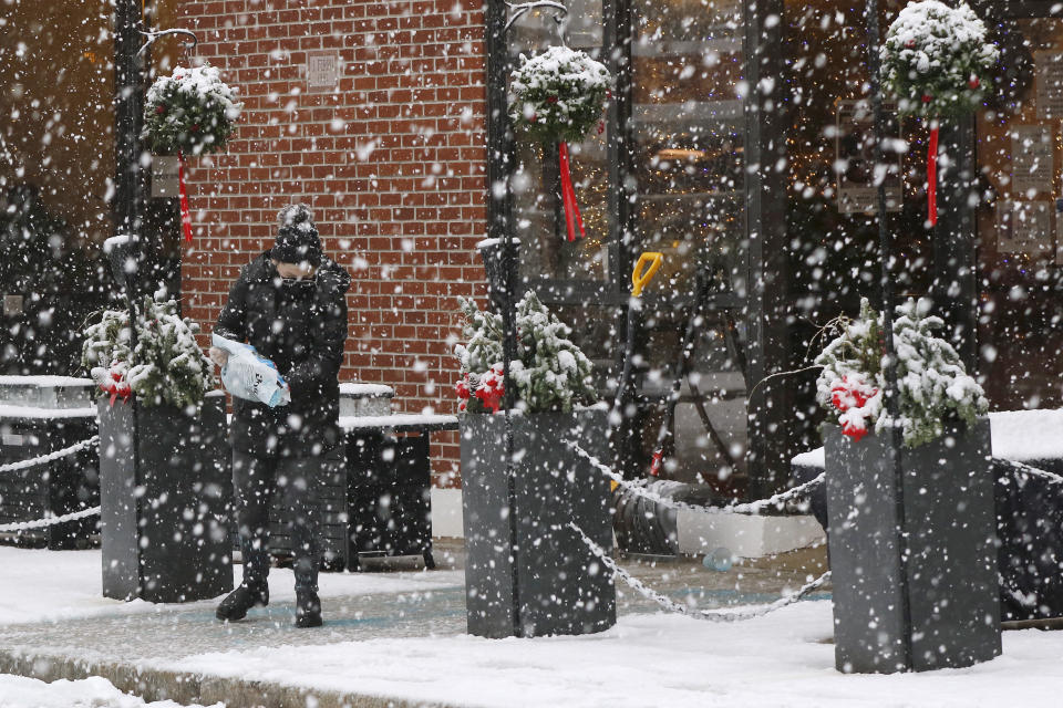 A worker pours ice melting pellets on the walkway outside a restaurant, Saturday, Dec. 5, 2020, in downtown Marlborough, Mass. The northeastern United States is seeing the first big snowstorm of the season. (AP Photo/Bill Sikes)
