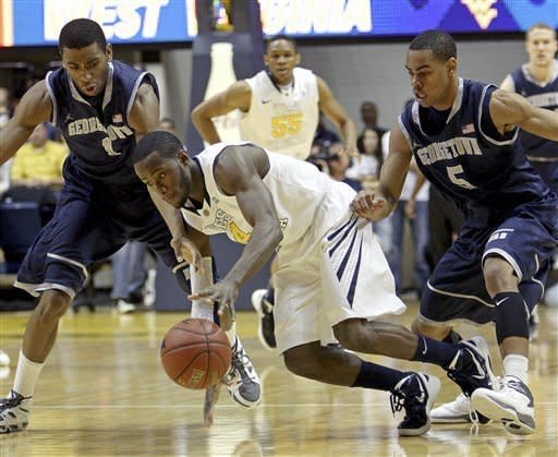 Georgetown's Hollis Thompson, left, and Markel Starks (5) guard West Virginia's Jabarie Hinds (4) during the first half of an NCAA college basketball game at WVU Coliseum in Morgantown, W.Va., on Saturday, Jan. 7, 2012. (AP Photo/David Smith)