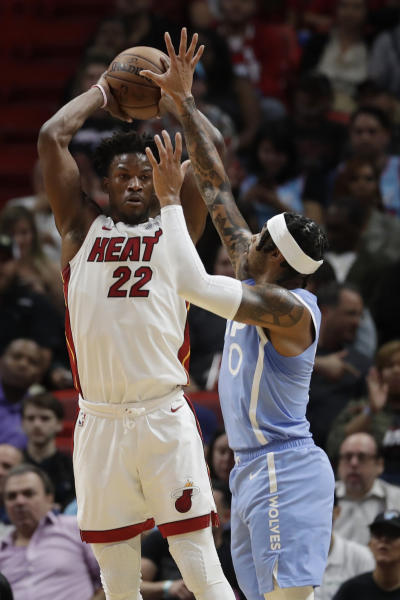 Miami Heat forward Jimmy Butler (22) passes past Minnesota Timberwolves guard D'Angelo Russell (0) during the first half of an NBA basketball game, Wednesday, Feb. 26, 2020, in Miami. (AP Photo/Wilfredo Lee)