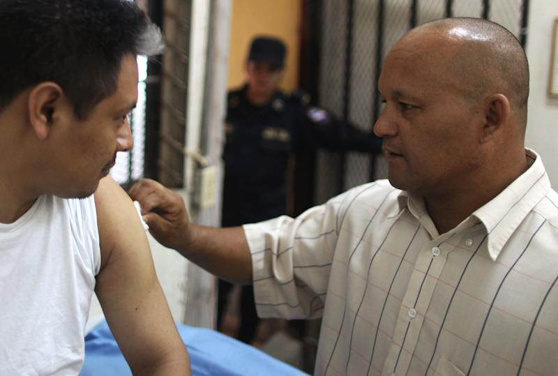 Inmate Marco Antonio Bonilla Avila, an assistant to the prison doctor, right, swabs the upper arm of a fellow inmate injured in the deadly prison fire, in Comayagua, Honduras, Wednesday Feb. 22, 2012. Bonilla, a 50-year-old convicted killer, has become Honduras' national hero after helping save hundreds of Comayagua prison inmates from dying in the Feb. 14 night fire; opening the doors to nine of the 10 barracks. Bonilla had been allowed to sleep in the infirmary in the last year instead of the barracks so he could tend to medical emergencies during the night. (AP Photo/Esteban Felix)