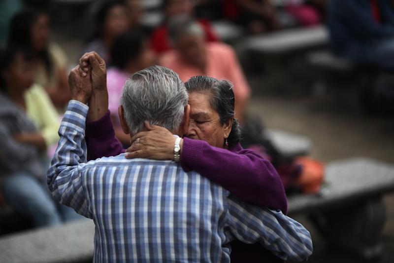 FILE - In this June 13, 2012 file photo, a couple dances in a public park in Guatemala City. A poll released Wednesday of nearly 150,000 people around the world says seven of the world's 10 countries with the most upbeat attitudes are in Latin America. Many of the seven do poorly in traditional measures of well-being, like Guatemala, a country torn by decades of civil war followed by waves of gang-driven criminality that give it one of the highest homicide rates in the world. (AP Photo/Rodrigo Abd, File)