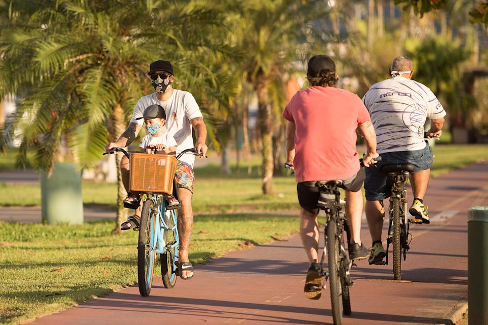 Santos, Brazil. May 09, 2020. Father walking his son on a bicycle during quarantine in Santos, Brazil.