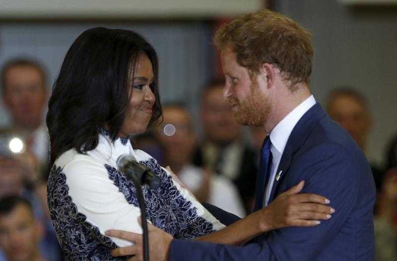 Britain's Prince Harry and first lady Michelle Obama embrace while making remarks during a visit to Fort Belvoir, Virginia October 28, 2015. Prince Harry is at Fort Belvoir to meet soldiers and spread the word about the Invictus Games, which supports wounded warriors. Prince Harry spearheaded the Invictus Games, which was first held in London last September. The next Invictus Games is planned for May in Orlando, Florida. REUTERS/Kevin Lamarque