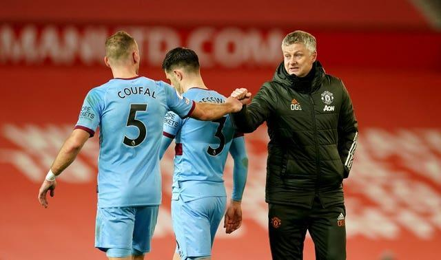Ole Gunnar Solskjaer, right, bumps fists with West Ham's Vladimir Coufal after the game