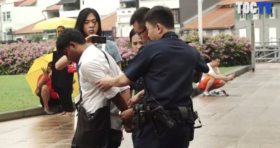 Activist and artist Seelan Palay was arrested outside Parliament House on 1 October 2017 by police officers. (PHOTO: Screenshot of video from The Online Citizen Facebook page)