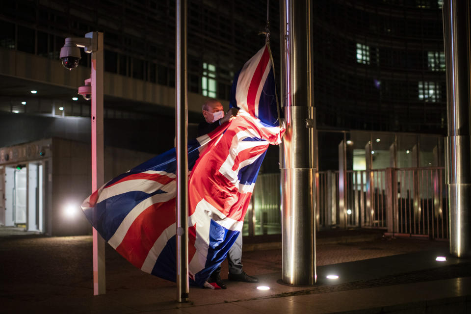 FILE - In this Wednesday, Dec. 9, 2020 file photo, a worker raises the Union Flag prior a meeting between European Commission President Ursula von der Leyen and British Prime Minister Boris Johnson at EU headquarters in Brussels. Relations between the European Union and recently departed Britain took another diplomatic dip on Wednesday, March 10, 2021 when the EU envoy in London was summoned to explain comments that Britain had issued a vaccine export ban. (AP Photo/Francisco Seco, File)