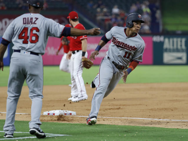 Minnesota Twins third base coach Tony Diaz sends Jorge Polanco home, scoring on a C.J. Cron single in the fourth inning of a baseball game against the Texas Rangers in Arlington, Texas, Thursday, Aug. 15, 2019. Miguel Sano also scored on the hit. (AP Photo/Tony Gutierrez)