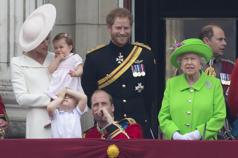 (L-R) Britain's Catherine, Duchess of Cambridge holding her daughter Princess Charlotte, Prince George, Britain's Prince William, Duke of Cambridge, Britain's Prince Harry and Britain's Queen Elizabeth II stand on the balcony of Buckingham Palace to watch a fly-past of aircrafts by the Royal Air Force, in London on June 11, 2016. Trooping The Colour and the fly-past are part of a weekend of events to celebrate the Queen's 90th birthday. / AFP / JUSTIN TALLIS (Photo credit should read JUSTIN TALLIS/AFP via Getty Images)