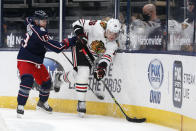 Chicago Blackhawks' Nikita Zadorov, right, tries to clear the puck as Columbus Blue Jackets' Cam Atkinson defends during the second period of an NHL hockey game Thursday, Feb. 25, 2021, in Columbus, Ohio. (AP Photo/Jay LaPrete)