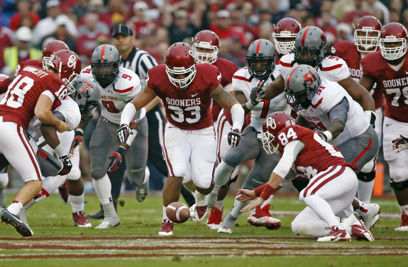 Texas Tech's Branden Jackson (9) and Kerry Hyder (91) and Oklahoma's Michael Hunnicutt (18) Trey Millard (33) and Mike Onuoha (84) chase a loose ball after a blocked Oklahoma kick in the first quarter of an NCAA college football game in Norman, Okla., Saturday, Oct. 26, 2013. (AP Photo/Sue Ogrocki)