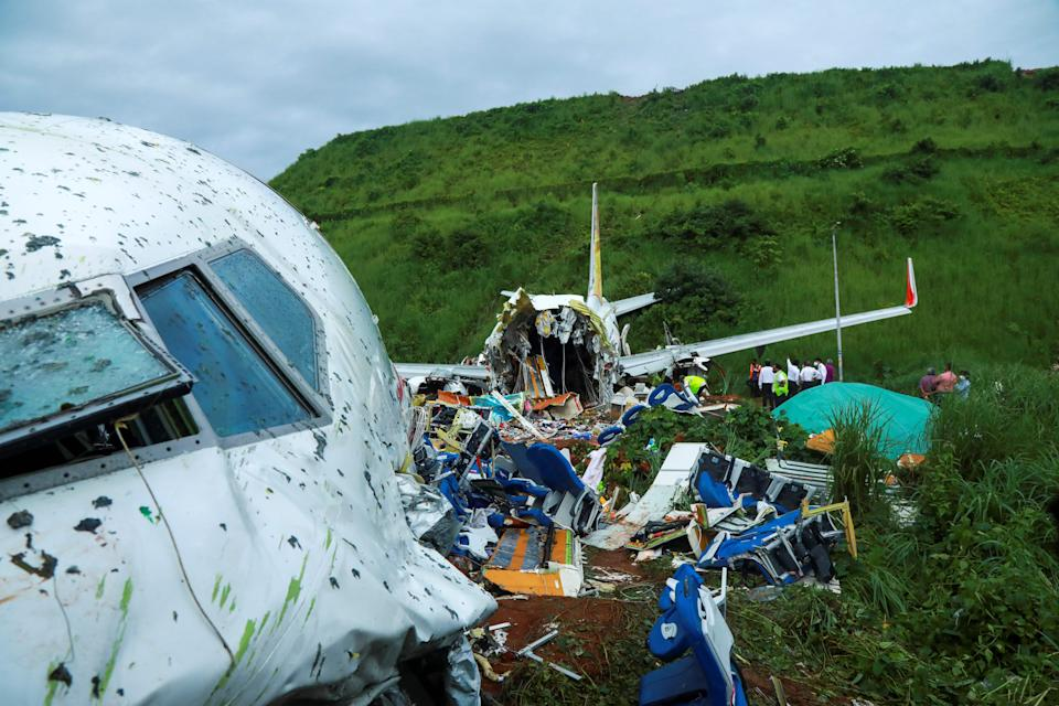 Officials inspect the wreckage of an Air India Express jet at Calicut International Airport in Karipur, Kerala, on August 8, 2020. - Fierce rain and winds lashed a passenger jet carrying 190 people from Dubai that crash landed and tore in two at an airport in southern India killing at least 18 people and injuring scores more, officials said. (Photo by Arunchandra BOSE / AFP) (Photo by ARUNCHANDRA BOSE/AFP via Getty Images)