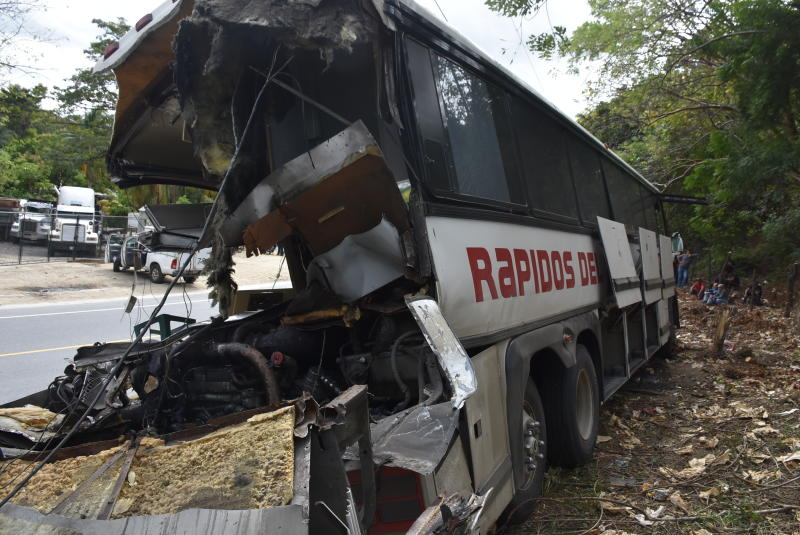 The wreckage of a passenger bus that crashed with a trailer truck lays on the side of the highway in Gualan, Guatemala, Saturday, Dec. 21, 2019. The early morning accident killed at least 21 people and left a dozen wounded, according to the national disaster agency. (AP Photo/Carlos Cruz)