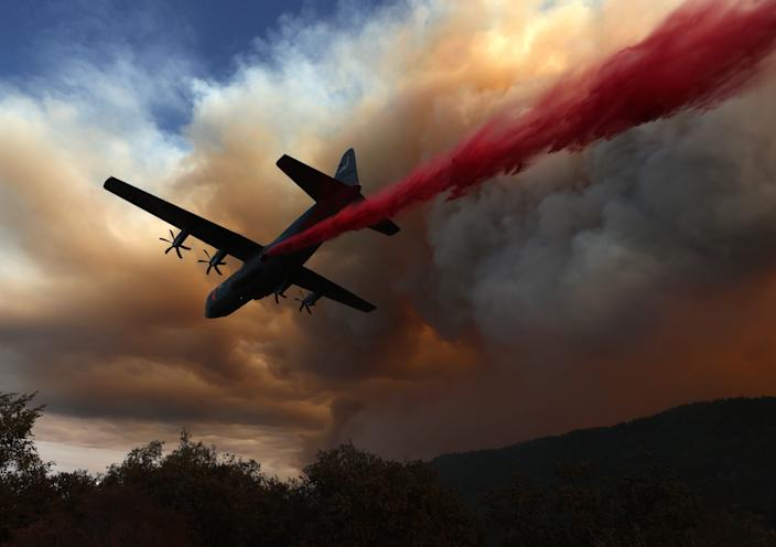 A C-130 aircraft equipped with Modular Airborne Fire Fighting Systems (MAFFS) drops retardant ahead of the LNU Lightning Complex Fire on Aug. 20 in Healdsburg, Calif.