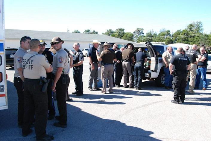 Officers from the surrounding areas join the Weatherford police in Weatherford, Okla., Tuesday, Sept. 24, 2013, to search for convicts that escaped during transport. The inmates were from jails in the western and northern United States and were being transported among agencies in the same regions of the country. (AP Photo/Weatherofrd Daily News)