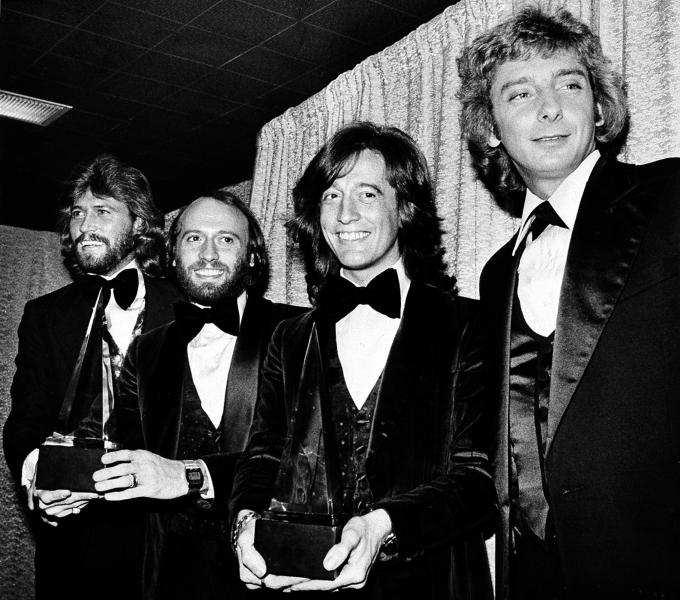 "In this Friday, Jan. 13, 1979 file photo, members of the Bee Gees pose with Barry Manilow, far right, at the American Music Awards in Los Angeles, Ca. The brothers Gibb, from left, Barry, Maurice, and Robin, won awards for favorite popular group and favorite soul album for ""Saturday Night Fever."" A representative said on Sunday, May 20, 2012, that Robin Gibb has died. He was 62. (AP Photo/Nick Ut, File)"