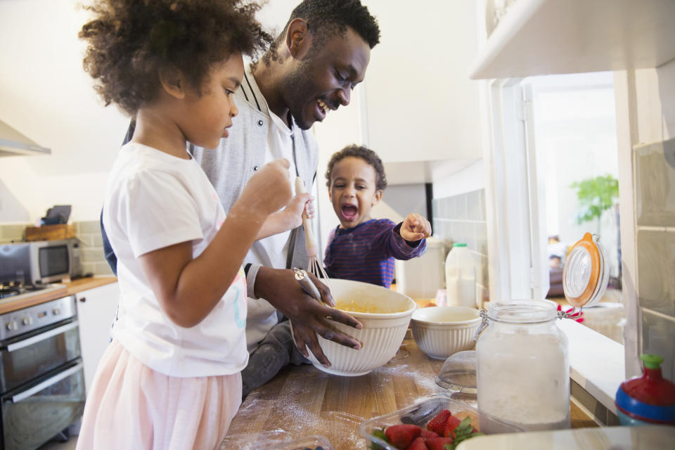 Father and toddler children baking in kitchen