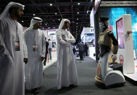 FILE PHOTO: Visitors look at an operational robot policeman at the opening of the 4th Gulf Information Security Expo and Conference (GISEC) in Dubai, United Arab Emirates, May 22, 2017. REUTERS/Stringer/File Photo