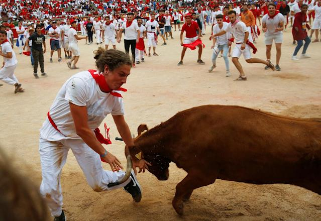<p>A reveler tries to dodge a wild cow following the last running of the bulls at the San Fermin festival in Pamplona, northern Spain, July 14, 2017. (Photo: Susana Vera/Reuters) </p>