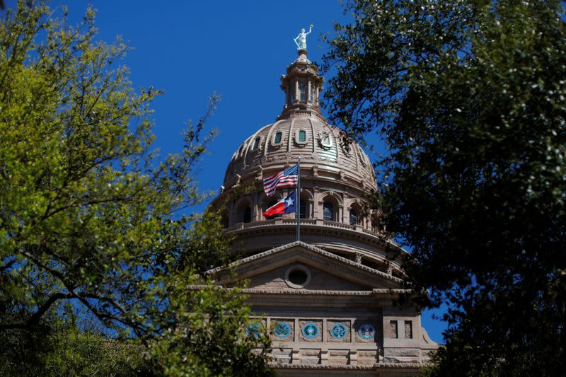 The U.S flag and the Texas State flag fly over the Texas State Capitol in Austin