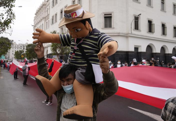 A supporter of presidential candidate Pedro Castillo carries a puppet in Castillo's likeness during a march in Lima, Peru, Wednesday, June 9, 2021. Peruvians are still waiting to learn who will become their president next month as votes from Sunday's runoff election continued to be counted and the tiny difference between the two polarizing populist candidates narrowed. (AP Photo/Martin Mejia)