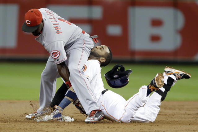 Cincinnati Reds second baseman Brandon Phillips, left, reaches back to tag out Houston Astros' Jonathan Villar as he tries to stretch a single in the first inning of a baseball game Tuesday, Sept. 17, 2013, in Houston. (AP Photo/Pat Sullivan)
