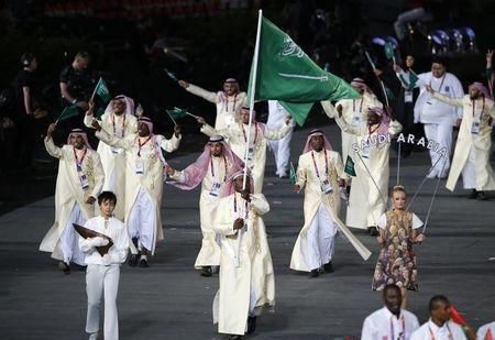 Saudi Arabia's flag bearer Sultan Mubarak Al-Dawoodi (C) holds the national flag as he leads the contingent in the athletes parade during the opening ceremony of the London 2012 Olympic Games at the Olympic Stadium July 27, 2012. REUTERS/Mike Blake