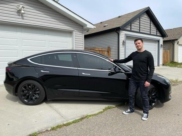 William York is a director with the Electric Vehicle Association of Alberta. He's pictured here next to his 2018 Tesla. (William York - image credit)